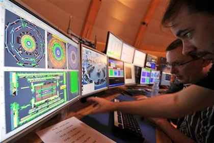 scientists look at a computer screen at the control center of the CERN in Geneva, September 10, 2008
