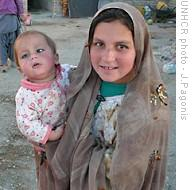 Afghan girl carrying her infant sibling in Iran's Sistan Baluchistan province