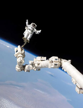 Astronaut Stephen K. Robinson, STS-114 mission specialist, anchored to a foot restraint on the International Space Station's Canadarm2