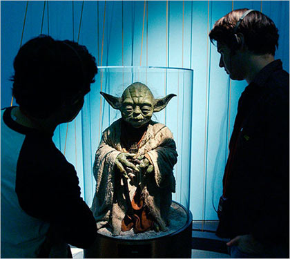 visitors inspect the puppet for Yoda, at the 'Star Wars — The Magic of Myth' exhibition in at the Brooklyn Museum of Art in 2002