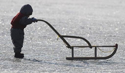 child pushing sled on frozen pond in Munich, Germany