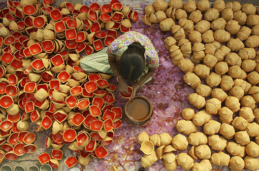 Diwali is marked by the lighting of lamps like these being prepared by a laborer in Amritsar