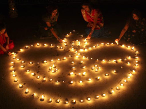 women light lamps in Ahmedabad, Western India, on the eve of Diwali, the Hindu festival of lights