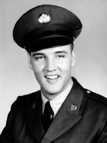 Elvis Presley smiles for a photo in his Army uniform