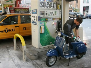 New York resident Austin Rommett fills his scooter with fuel at a gas station in New York