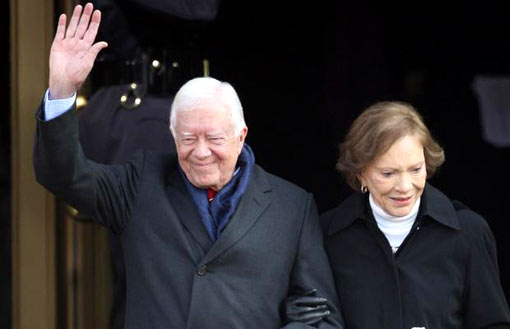 Former President Jimmy Carter is accompanied by his wife, Rosalynn, as he waves to the assembled crowds