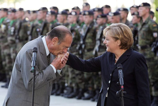 French President Jacques Chirac kisses the hand of German Chancellor Angela Merkel upon his arrival at the Chancellery May 3, 2007 in Berlin, Germany