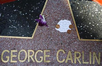 a note and a flower are seen on the star of comedian George Carlin on the Walk of Fame in Hollywood