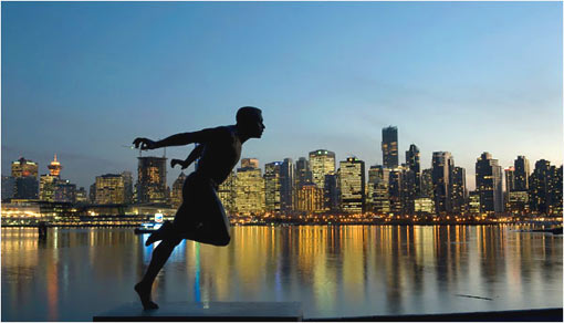 A statue of runner Harry Jerome stands against the Vancouver skyline