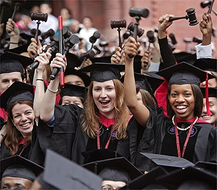 Harvard graduates raise their gavels during commencement ceremonies