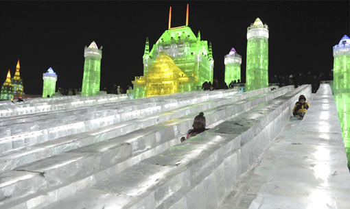 visitors sliding down ice slides at 25th Harbin International Ice and Snow Festival