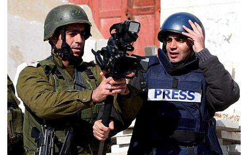 an Israeli army officer (L) grabs a video camera from Reuters cameraman Yusri al-Jamal as he prevents him from covering news events in the West Bank city of Hebron