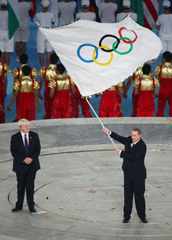 Jacques Rogge, President of the International Olympic Committee waves the Olympic flag watched by London Mayor Boris Johnson during the Closing Ceremony for the Beijing 2008 Olympic Games