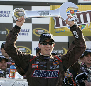 Kyle Busch poses with trophy after winning Kobalt Tools 500 auto race