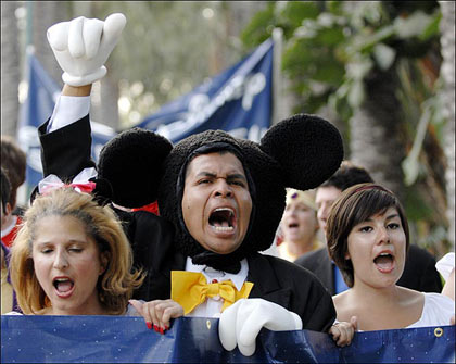 hotel workers march from the Paradise Pier Hotel to the main entrance of Disneyland