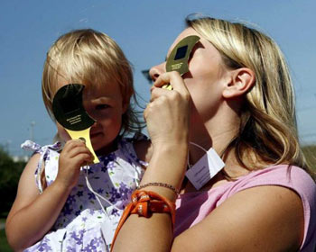 mother and child use a special eye protection device as they watch the partial solar eclipse in Riga 1 August 2008