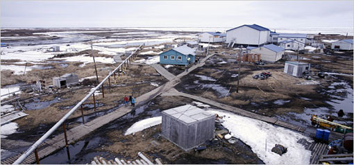 Newtok, Alaska, in spring, 2007, as viewed from its water tower. Boardwalks squish into the muck in Newtok, which erosion has turned into an island