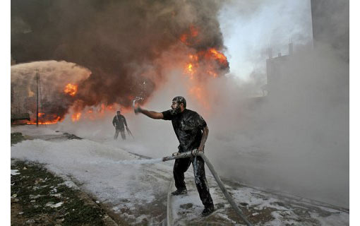 Palestinian firefighters try to put out flames in a refuge camp building
