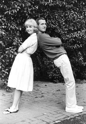 American actors Joanne Woodward and Paul Newman lean back to back on each other outdoors, in the early 1960s, a few years after they married