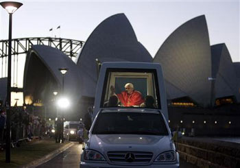 Pope Benedict XVI waves to pilgrims as he passes the Sydney Opera House in his Popemoblie after addressing thousands at Barangaroo on his first day of official duties during World Youth Day activities, July 17, 2008