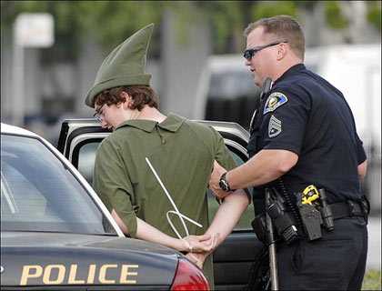 police officer arrests demonstrator dressed as Peter Pan during protest against Disney's treatment of hotel workers outside of Disney Land in Anaheim, California