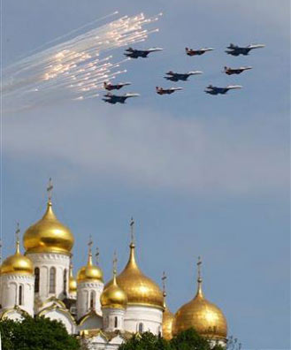Russian fighter jets launch flares as they fly above the Moscow Kremlin cathedrals' gold-plated domes