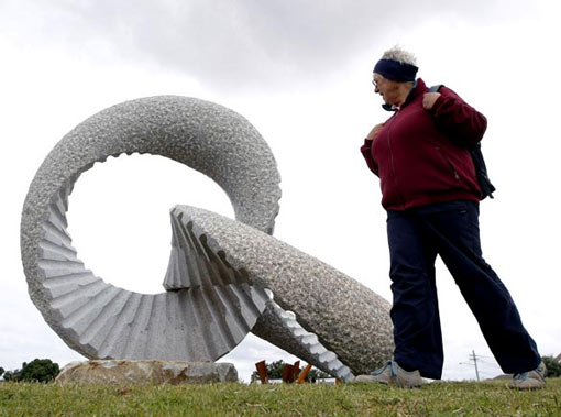 a woman inspects a work by Japanese artist Keizo Ushio