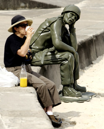 a visitor to Sydney's Tamarama Beach enjoys a refreshment near a sculpture titled Soldier Scale 1:1