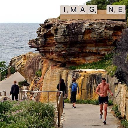 a jogger passes the timber and aluminium work 'IMAG_NE' by Australian artist Emma Anna