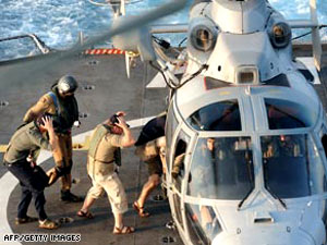 three British security guards board a helicopter to be transferred to a Royal Navy vessel