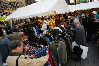 Tents selling secondhand clothes are crowded in front of a busy train station in Tokyo Monday, Nov. 17, 2008