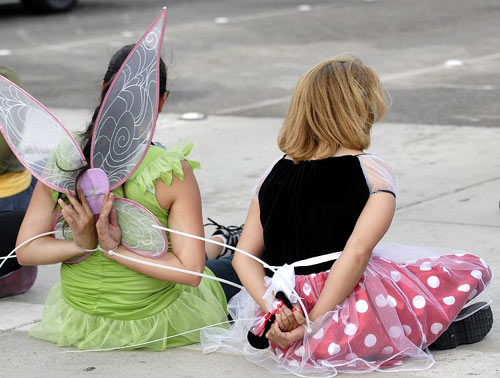 Cinderella, Snow White, Tinkerbell and other fictional fixtures of modern-day childhood arrested outside Disneyland