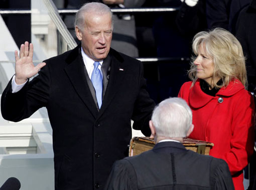 Vice President-elect Joe Biden takes the oath of office from Justice John Paul Stevens as Mr Biden's wife Jill holds the Bible