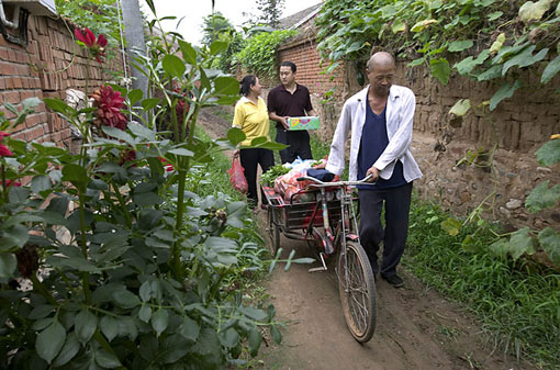 Weitaiwu Village, China: Bicycle Delivery; the Cui family carries goods home from the market on a sanlun che, a type of three-wheeled cart