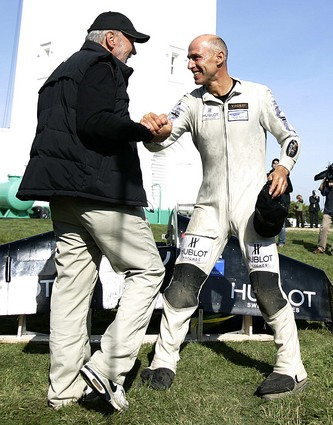Landing near Dover, England, Yves Rossy, right, accepts congratulations after flying his jet-propelled wing over the English Channel. His flight took just 10 minutes