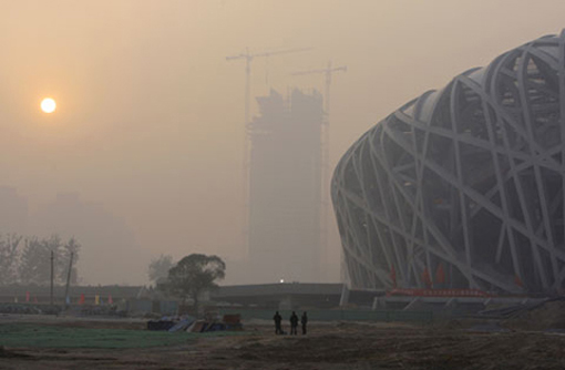 There's no denying that Beijing's skies are gray everyday. Workers stand near the Olympic Stadium (R), also known as