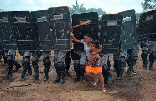 woman holding her naked child while being pushed away from her home by a line of riot police