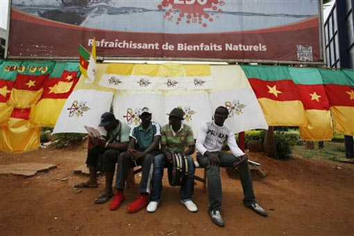 Cameroonian salesmen wait for customers in front of a display of Cameroonian flags and locally-made Vatican City flags, which they commissioned for Pope Benedict XVI's visit, in central Yaounde, Cameroon Monday, March 16, 2009. Pope Benedict XVI will arrive in Cameroon Tuesday on his first trip to Africa, the fastest-growing region for the Roman Catholic church