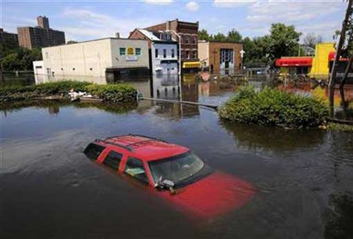 Flood waters from the Passaic River fill the streets covering automobiles including a Chevrolet SUV days after Hurricane Irene in Paterson, New Jersey, August 31, 2011.