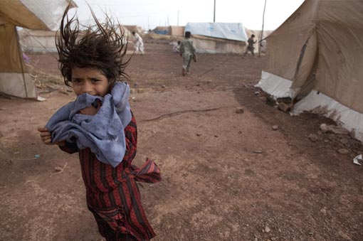 a girl stands next to her tent as wind and rain pass through the tent city at Jalozai camp on June 2, 2009, 15km from Peshawar, Pakistan