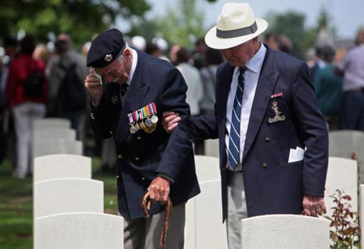 Normandy Veteran Fredrick William Norris, who was awarded the Military Medal, passes the graves of friends from his regiment, the 5th Assualt Regiment of the Armoured Engineers