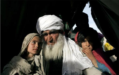 Sayed Abdul Karim, 80, sits with his 9-year-old granddaughter, Camina, left, in a camp for displaced Afghans 3 hours from their village