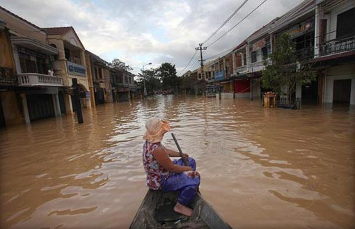a woman surveys the flooded streets of Hoi An from a boat