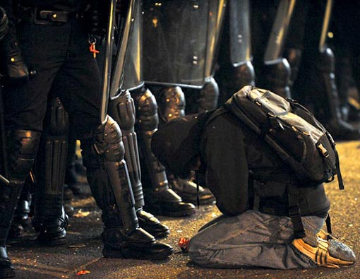 a man kneels in front of police officers during clashes with demonstrators in Paris