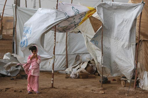a girl stands next to her tent as wind and rain pound the massive tent city June 2, 2009 at Jalozai camp, 15km from Peshawar, Pakistan