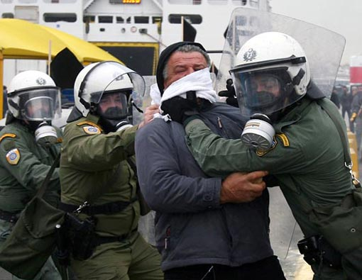 riot police arrest a farmer after he attempted to back his tractor into a group of police at the main port of Piraeus