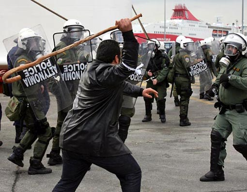 after nearly two weeks of demonstrations, Greek farmers used their tractors to block border crossings and highways across the country for days, demanding financial help from the government. A farmer hits a riot police officer with his crook at the main port of Piraeus, near Athens, Feb. 2, 2009