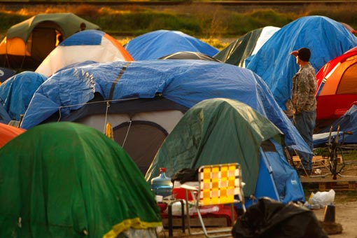 a homeless man looks out over tent city as the sun sets in Sacramento