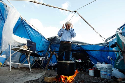 Gennadiy Petrovich Tomashov, 57, prepares soup over an open fire. Tomashov, a homeless truck driver, has been living in tent city for the last eight months