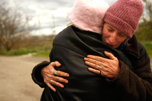 Jackie Dickens, right, receives a hug of support from Renee Hadley. Both of them have been living in tent city for the last year